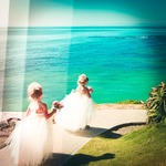 Flower girls holding bouquets walking along the beach by Wedding Photographers San Diego Andrew Abouna