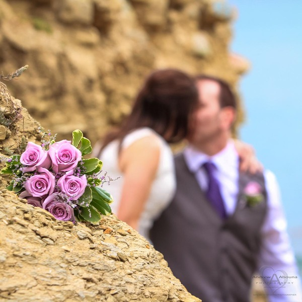 Lavender rose bouquet with bride in jewel wedding dress and groom with grey vest purple tie boutonniere kissing in background by Wedding Photographer San Diego Andrew Abouna